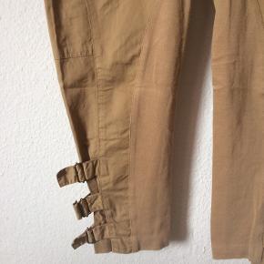 By Malene Birger - bukser Str. 34 Næsten som ny Farve: kamel farvet Lavet af: Shell: 100% cotton Trimming: 70% viscose, 25% polyamide og 5% elasthan Mål: Livvidde: 74 cm hele vejen rundt Længde: Ydre: 92 cm Indre: 65 cm Køber betaler Porto!  >ER ÅBEN FOR BUD<  •Se også mine andre annoncer•  BYTTER IKKE!