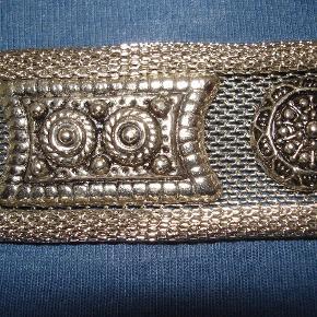 """Varetype: lækkert, anderledes, råt """"sølv""""-bælte med dekorationer Størrelse: 85X 3 cm Farve: """"Sølv""""  Superflot anderledes sejt og råt """"sølv""""-bælte med dekorationer fra antikken. Måler 85/90 X 3 cm. Brugt få gange og fremstår i meget flot stand. BYTTER IKKE"""