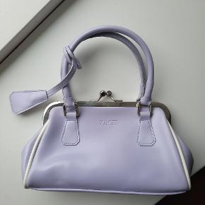 Super cute handbag! Never been used. The material is faux leather in light purple/lilac.  The bag has one main compartment & a small zipped pocket. It also has a keychain!