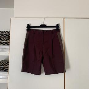 Sælger disse shorts fra Wood Wood. De Bordeaux og har lysebrune stribe ned af benet og har lommer. De er lavet af 44% uld og 54% polyester og 2% elastan☺️