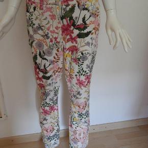 Cambio Jeans 44, hvide med blomster print, model Parla, 98% bomuld/2% elastan MÅL: Livvidde 96 cm, indv skridt 68cm Brugt 1 gang, er som NYE! (kr 1299)