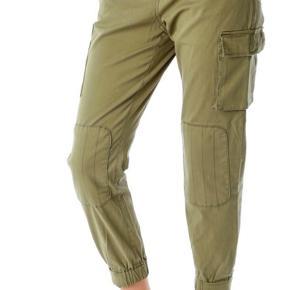 Super fede cargo bukser med elastik i benkanten. Udvendig kuvert lomme på på side af venstre ben, på højre ben er der udvendig lynlås lomme. Skrå lommer i hver side og lommer bagpå. Lap på hvert knæ.  Nye med tag.  Bytter gerne til str 40  Farve: Army (Dark olive) Materiale: 97% Bomuld, 3% Elastane.  Nypris 999kr   Militær / army bukser model