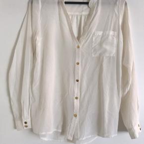 Cremehvid see-true skjorte i silke.  Knapperne har lidt skrammer, se billede. Pris sat efter stand. Np: 1499kr.  Mål:  Længde: 67 cm Bryst: Ø 104 cm