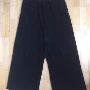 Fine løse bukser med elastik i taljen og lommer. Stoffet er stretch, rib og lidt shiny.