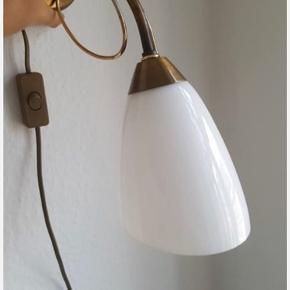 Smuk gammel væglampe i messing (messing-lignende materiale) med opalglas skærm. Skøn patina.  Man kan evt føre ledningen ud af et andet hul, så man selv kan vælge om lampen skal vende op eller ned.   Afhentning i Aarhus N (trøjborg)