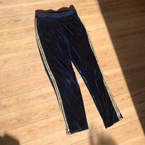 Super fede bukser i loose fit fra Vero Moda i str. L ❄️ i velour oh med guld/sort stribe på hver side. Pisse fede! Mørkeblå farve. Brugt et par gange, men i god stand.   Bemærk - afhentes ved Harald Jensens plads eller sendes med dao. Bytter ikke 🌸  💫 Bukser joggingbukser pants jogging bukser blå mørkeblå mørke blå velour guld sort stribe striber stribet