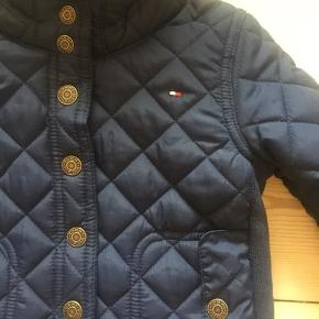 Fin Tommy Hilfiger quiltet jakke med hætte, lommer med knapper, piping og fleece for. Aldrig brugt da min datter var for stor da det blev årstid for den.  Flere billeder kan sendes. Str. 12 måneder, men vil mene det er en str. 74  Sendes på købers regning eller afhentes i Århus. Kommer fra ikke ryger hjem  Unisex model.