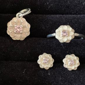 🌸 Sæt fra Pandora 🌸  Alle dele er m/lyserød emalje og lille pink zirconia sten.  Vedhæng - måler ca 8 mm Ring str. 54 - blomsten måler ca 6 mm Ørestikker - måler ca 5 mm  Alle dele fremstår som nye uden brugsspor eller ridser.