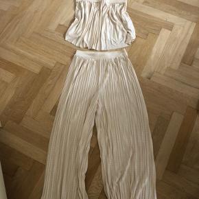 Festligt sæt fra H&M. Er ikke hvidt, men mere perlemorsfarvet. Buksebenene er brede og går til midt på læggen ca. Der er to små pletter på bukserne. Sælges kun samlet.