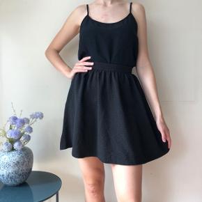Flot sort nederdel med mønstret stof. Brugt få gange 🌸