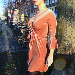 Den sødeste lyserøde fløjls kjole. Skørt til midt lår, cross udskæring, og bindes under under brystet. Kjolen har en flot og sød farve med et fint skær i lys. Den er god varm i det kolde festlige dage. Jeg sælger kjolen da jeg desværre ikke får gået med den.  #trendsalesfund