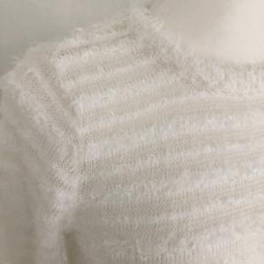 Fin strikbluse med lange ærmer fra Sisters Point str. M i råhvid. Blusen har skiftevis fint hulmønster og lidt frynser.  Længde fra skulder er 60 cm, og brystmålet er 102 cm. Vaskeanvisningen er svær at tyde, men eller er blusen i rigtig pæn stand.