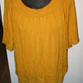 Varetype: T-shirt Farve: Carry gul  Bryst 2x60 cm. Længde 65 cm. 92% viscose og 8% elastane.  Kom med et friskt bud på mine vare, alle bud tages seriøst, nogle syntes 40 Kr. er mange penge mens andre syntes det er et greb i lommen. hvis jeg syntes det er for lidt, kan vi vel forhandle lidt, der bliver ingen sure svar tilbage. Enten kan vi blive enige eller også bliver der jo bare ingen handel  Se også mine andre vare, har rigtig mange. Det er nu også blevet muligt for mig at sende med Dao, så skriv hvis man ønsker det, de priser jeg har på annonce porto er post DK. Den kan sendes for 37 Kr. Med Dao.