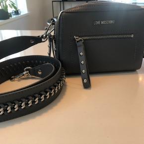 Super smuk og næsten aldrig brugt  Grå Love Moschino taske, i super fin stand. Næsten aldrig brugt. Exklusiv fragt. Kontakt gerne for flere billeder mm.  Normal pris: 849 kr.