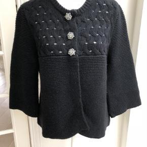 Varetype: Strikjakke Farve: Sort  Smukkeste strikcardigan i uld og cashmere fra Style Butler. Cardiganen har et flot hulmønster foroven samt nogle super fantastiske knapper.