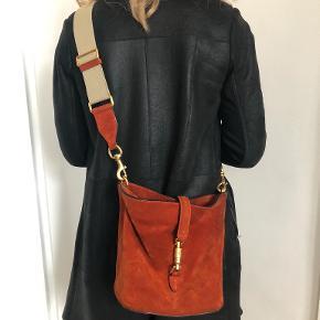 Den ikoniske Jackie taske i den smukkeste farve. Kommer med to remme, en i ruskind som tasken og den anden i kanvas. Desuden en lille makeup pung i samme mat. Mål: H 25,5cm, B 23cm, D 16,5cm. Ingen huller og lign. Kun patina efter brug;)