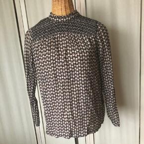 Bluse i dejligt blødt materiale, kinakrave, smocksyning øverst, lukkes i ryggen med små knapper, der går hele vejen ned.