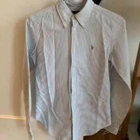 Klassisk blå/hvid-stribet skjorte fra Ralph Lauren sælges. Pasformen er super slim fit, hvilket giver den et feminint udtryk. Hvis varen skal sendes, betaler køber fragten.