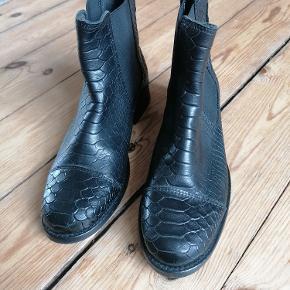 Fra Shoe Biz Copenhagen. Sorte skindstøvler med elastik i siden.  Aldrig brugt. Kun prøvet på indendøre.  Slangeskinds-prægning som mønster.  Str. 36. Lidt store i størrelse.  Mat skindtone.  Nypris i butik: 899 Kr. Kan afhentes i Esbjerg eller sendes. Angivet pris er excl. fragt.