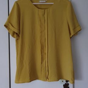 Flot skjorte bluse i dæmpet gul. Brugt få gange.  Kig forbi mine andre annoncer og spar penge - også på portoen 😉