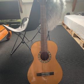 Sælger denne fine sag af en guitar. Den har udelukkende stået til pynt på mit værelse, men to af strengene er gået i stykker med årene☺️  Jeg kan yderligere kontaktes på: 333andrea@live.dk 26845491