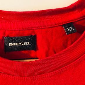 Varetype: T-shirt Farve: Rød Oprindelig købspris: 499 kr. Kvittering haves.  Super frisk og behagelig T-shirt fra Diesel med stort print af deres kendte mohikaner på front sælges da det skal ryddes op i tøjskabet.  T-shirtsen er købt hos Diesel i Kbh og fremstår som ny da den nærmest aldrig har vært båret siden købet.  Ingen form for pletter, misfarvning el.  Giv et fair bud.
