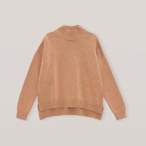 Helt nyt  100% merino  Str. S/m    Chunky mock-neck jumper in merino wool with side slits, and ribbed hem details. Pair with shorts or jeans for an effortless look. Oversized cropped silhouette Pullover style Longer in the back with side slits Ribbed accents Dropped shoulders Soft, heavyweight knit, 100% merino wool Made in Italy