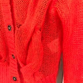 Sælger denne flotte cardigan i flot rød farve. Sælger billigt da den har et lille hul (det er repareret). Hullet er et sted hvor man ikke bemærker det... Skriv for flere billeder af reparationen. Kan hentes på vestebro.