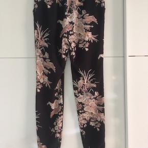 Lækre bukser fra Stella Nova i sorte med lyserødt fugleprint sælges. Str. 36. Brugt, men i fin stand. De er trukket lidt i stoffet enkelte steder, men ikke noget man ligger mærke til (se billede 3).