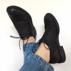 En klassisk derby sko i sort ruskind/læder, som har et mat udtryk.    Det er en størrelse 37, og normal i størrelsen. De er brugt 5-10 gange