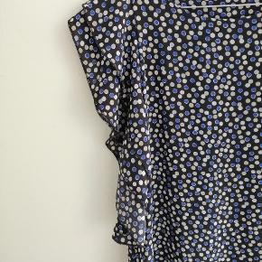 Sød kjole med prikker i lyseblå, mørkeblå og beige farver. Har flæser ved ærmerne og nederst