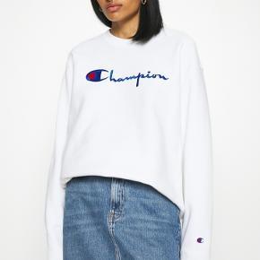"""Hvid sweatshirt fra Champions. Modellen hedder """"Champion Reverse Weave Crewneck"""" og har blå skrift på fronten. Trøjen er i str Large men er lille i størrelsen."""