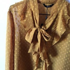 Karrygul skjorte fra ONLY  Aldrig brugt og stadig med prismærke i   Feminine flæser og bindebånd i halsen  Knapper ned langs forsiden   Str. 36