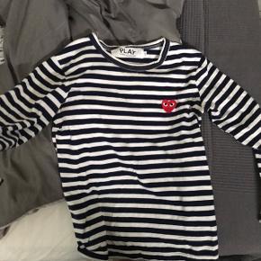 Play trøje Mørkeblå og hvid stribet.  Str S, men den er lille i størrelsen, så den ville bedre passe en Xs. Den er brugt lidt, men der er ingen tegn på slid. Byd