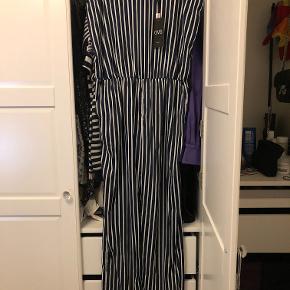 Helt ny stribet jumpsuit / buksedragt, stadig med mærke.  Mørkeblå og hvid stribet. Elastik i taljen og sløjfe lukning på skuldrene.   100% Polyester  Kom gerne med et bud! :D  Tjek gerne mine andre annoncer :D