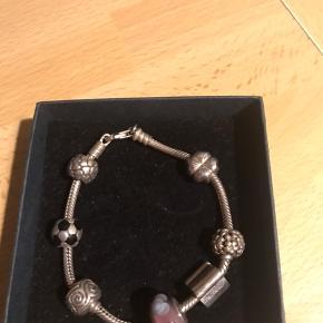 Fint Pandora armbånd i sølv med 7 stk charms . Armbåndet måler 19 cm incl lås. Sætter det til 500kr , men du er velkommen med et realistisk bud .