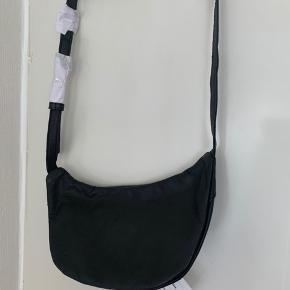 Sort lille skind bum bag / cross / bæltetaske (kan styles på flere måder) Bredde øverst knap 24 cm Bredde nederst knap 18 cm Højde ca 12-12,5 cm Regulerbar rem med mange huller knap 90 cm. Der er to rum og lille lynlås lomme i det største rum