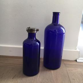 Den blå glas flaske med tin låget koster 175 kr  den blå flaske uden låg koster 125 kr.