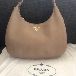 En ikonisk Prada taske! Meget smuk og praktisk. Rigtig godt stand, uden pletter inden eller udenfor. Det er lidt misfarvning på guld hardware, se på bilede. Mål: H 25x L34x B 14 cm. Købt i Tokyo i 2015. Kvittering haves ikke længere.