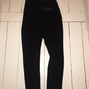 Højtaljede sorte bukser.