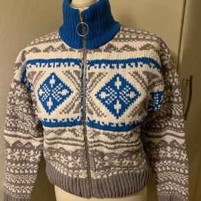 Kort sweater cardigan (blå, grå, hvid) fra UO i str. S. (Passes også af  M - se mål) Mål: Længde ca 50 cm Bredde fra ærmegab til ærmegab ca 50 cm uden at stretche. Ærmer fra lav skulderkant og ned ca 50 cm Materiale kraftigt strik i poly. Har den også i XS - se anden annonce! (Har selv en i brug, som jeg har vasket i vaskemaskine uden problemer) Nypris i UO 790 Sælges for langt  under halv pris plus porto. Hvis afhent 260 Eller 300 inkl med DAO, såfremt MobilePay