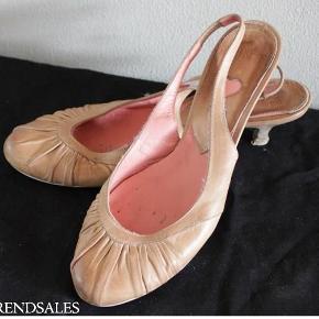 """Varetype: flade stilletter sko sandaler flats sommer ægte læder læderstilletter Størrelse: ca. 38 - 38.5 Farve: lys læder Oprindelig købspris: 600 kr.  ★. ★. ★ SMUKKE LAVE STILLETTER I ÆGTE LÆDER FRA BRINTS ★. ★. ★  Et par lækre lave stilletter fra Brints i ægte læder!  Skoene er rigtig fine og lækre og sidder godt på foden, da der er en rem med elastik, som sidder rundt over hælen. Skoene er mærket med størrelse 8, men jeg vil sige, at de passer de størrelsemæssigt er til den lille side og derfor bedst passer en størrelse 38 eller 38,5.  Skoene har flot rynke-læder fortil og er det indvendige er koralfarvet læder. Selve forsålen er i blød lys gummi, som gør dem rigtig behagelige at gå med. Hælhøjden fra hæl (fodsålen) og ned er 4,2 cm.  Skoene har været brugt et sted mellem 4 og 5 gange. De fremstår i flot stand med kun overfladisk slid på forsålerne. Den ene hæl ser rigtig fin ud, hvor der på den anden hæl er gået et lille hak af det nederste træ på hælen. Dette er minimalt og måler 2 x 4-5 millimeter og kan ses på billedet. Selve læderet på skoene har brugs-patina, som kom med det samme, da det er ubehandlet læder (se billeder), men jeg synes stadig, skoene ser fine ud og er perfekte til hverdagsbrug eller en casual fest her til sommer.  Jeg har oprettet skoene i kategorien God, men Brugt med de forbehold, som er nævnt ovenfor og kan ses på billederne. Jeg sælger kun disse flotte stilletter, da de altid har været liiiige det mindste til mig, og jeg nu desværre er """"vokset"""" helt fra dem, da mine fødder er blevet større efter graviditet. Jeg husker ikke nypris, men mener, den var ca. kr. 600,-. Grundet ovennævnte """"skavanker"""" sælges des ultrabilligt!  Skriv emailadresse for billeder i stort format, så du kan zoome ind og se alle detaljerne :-)  ★ PRIS kr. 89,- + brevporto på eget ansvar kr. 24,- ★  KOM GERNE forbi og prøv! SPAR PORTO ved afhentning i Esrum, Nordsjælland."""