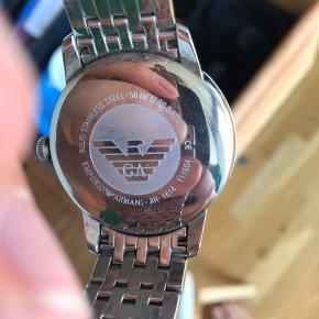 Armani ur i sølv.  Bemærk at uret går ikke da batteriet skal skiftes. Kan gøres hos urmager til ca. 100.  Der er meget små kosmetiske ridser i glasset. Er svært at se medmindre man kigger efter. Har prøvet at illustrere det på billederne. Uden æske