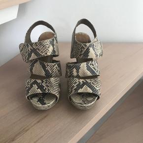 Super fine sandaler som kun sælges fordi min ryg ikke tillader hæle mere:-(.  Hælhøjde 8-10 cm alt efter hvor man måler fra, man mærker ikke højden, da der er plateau på 2 cm foran.  Kan sendes med Dao for 40 kr. eller afhentes i Århus C.