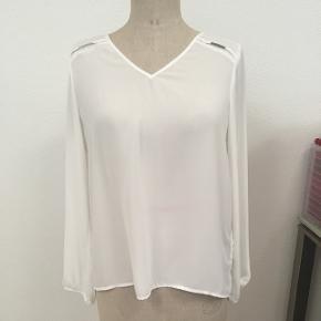 Blouse blanche avec détaille en imitation argent sur les épaulettes