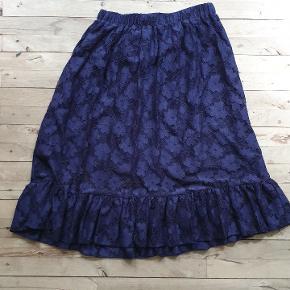 Mørkeblå blonde nederdel med flæse.  Mærket med størrelsen er klippet ud, men mener det er 42. Størrelse 40, 44 og 46 ville også kunne passe den.  Den måler 78 - 110 i taljen, 160 om rumpen og den er 76 lang. Nypris: 1500,-
