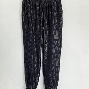 """Flotte bukser med skinnende leopard mønster. """"Jogging facon"""" med elastik og snøre i livet. Str s, alm i størrelsen. Ubrugte med tags. Bytter ikke."""