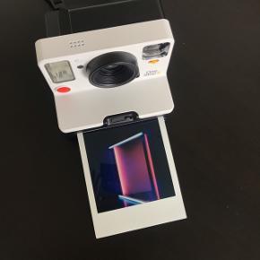 """Jeg sælger mit Polaroid OneStep 2 kamera i hvid. Kameraet er halvandet år gammelt, og fejler bestemt ingenting - det er stort set så godt som nyt!   Jeg sælger kameraet sammen med det originale opladningsstik samt den medfølgende brugermanual og """"skulderrem"""".   Kameraet bruger i-Type- eller 600 film og har en batteritid på 60 dage, samt en self-timer-funktion."""
