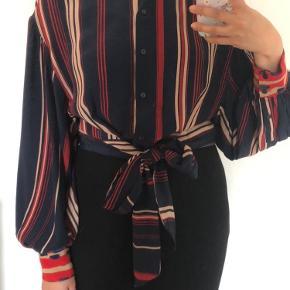 Skjorte med bindebælte, som kan bindes både forfra og bagfra