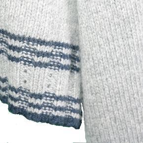 Lækker blød strik cardigan fra Custommade med fine detaljer. Langs kanten på ærmet samt ved åbningen, er et diskret hulmønster med blå striber.  God mellem tykkelse til de kolde sommeraftener. Brugt få gange. Style: Gaye. Farve: Lys grå med blå striber. Str. M - kan bruges lige fra small-large. Materiale: Angora, uld, nylon, viskose.   Køber betaler fragt med Dao eller kan evt afhentes på Østerbro.  Se også mine andre annoncer 🙂.
